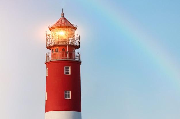 Lighthouse in baltiysk port. beautiful rainbow and beacon lights
