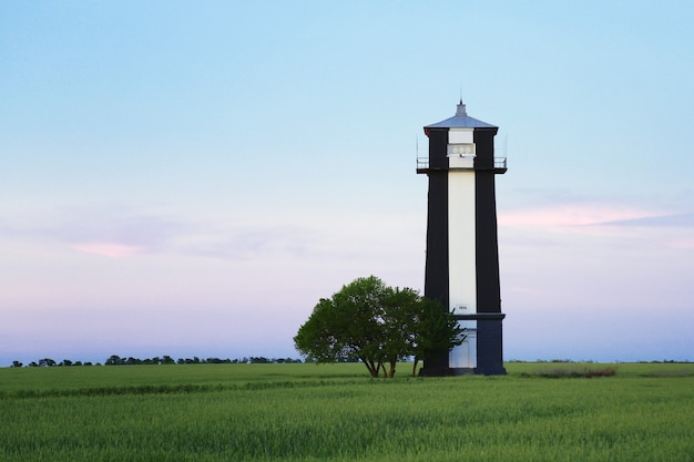 灯台の建物。古い黒と白の灯台の建物は、夏の日没時にフィールドの土地に立っています。