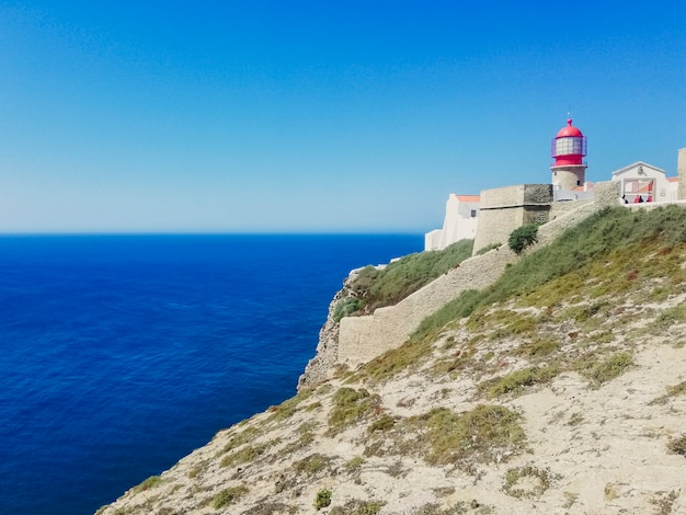 Lighthouse over cliff in sagres, portugal.