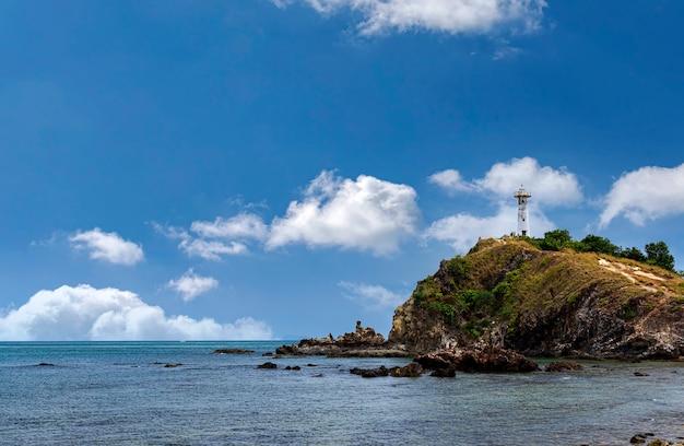 Lighthouse on a hill and beach under a sunrise sky
