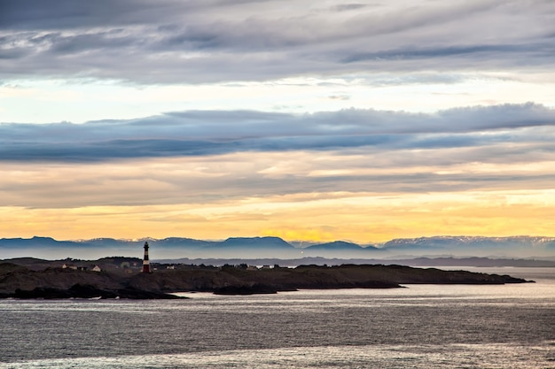 The lighthouse and mountains silhouette in dusk, norway