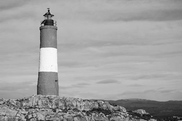 흑백에서 흐린 하늘을 배경으로 바위 섬에 등대