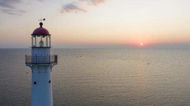 美しい夕日の間にエストニアのキフヌ島の灯台
