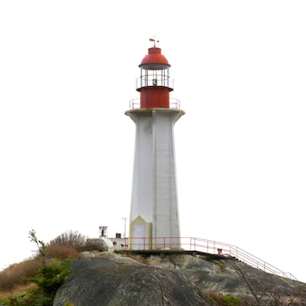 白で隔離された岩の上の灯台