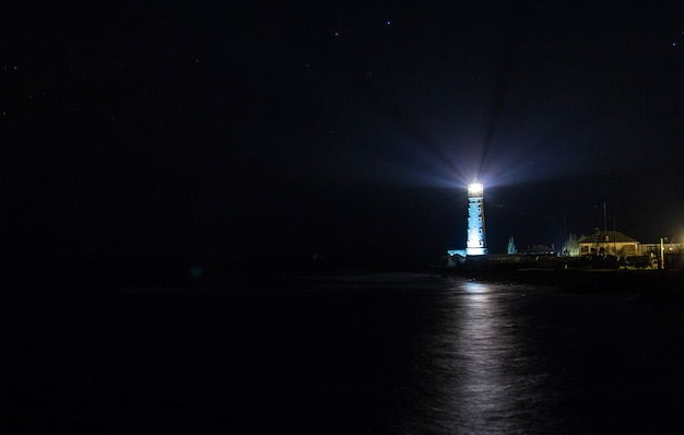 Маяк на берегу моря ночью