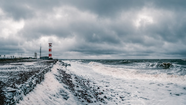 Маяк на берегу бушующего белого моря на кольском полуострове