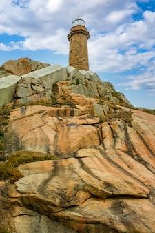 青い空と雲のある岩だらけの丘の上にある灯台。ガリシアスペイン。