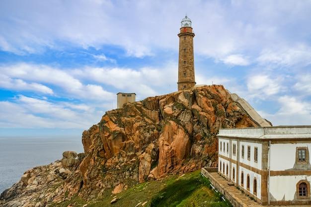 岩だらけの丘の上にある灯台。その隣に灯台守の建物があります。ガリシアスペイン。