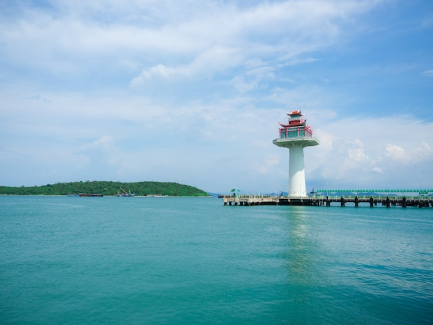 Lighthouse at port ship with mountain view landscape blue sky and ocean