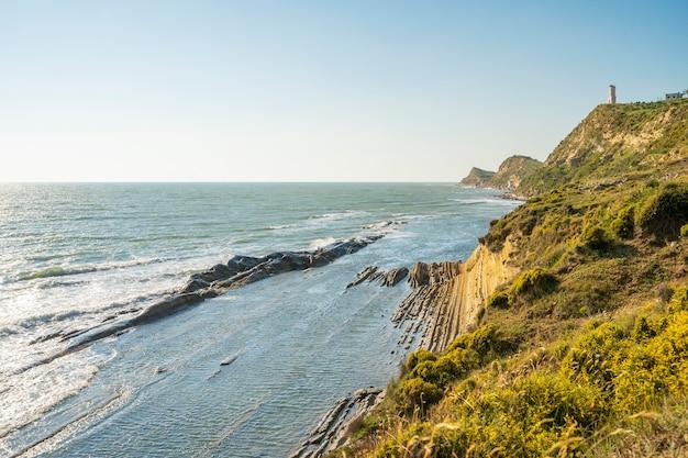灯台サーチライトは夜に海の空気をビームします。日没時の海景 Premium写真