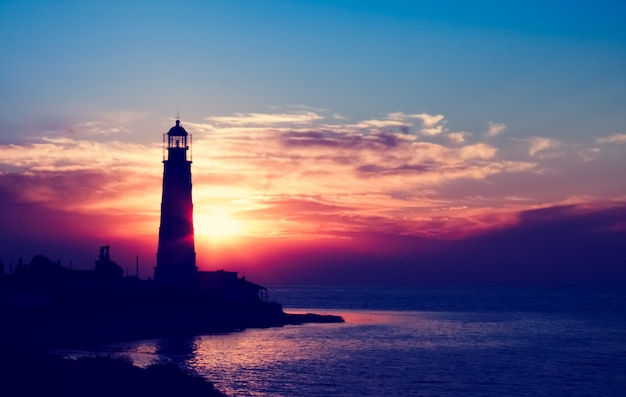 Lighthouse at the sunset on the beach