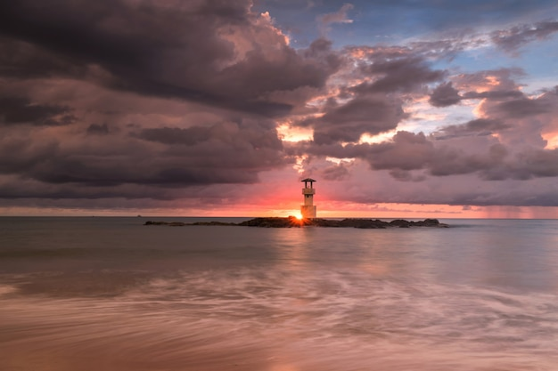 Lighthouse tower building against motion ocean wave, dark cloud, sunset, sumbeam at khao lak beach in phang nga,thailand. seascape at famous travel destination.