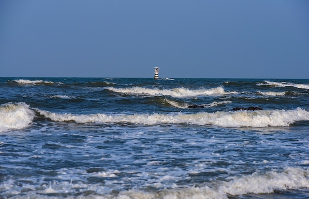 The lighthouse tower is in the middle of the sea on a clear blue day
