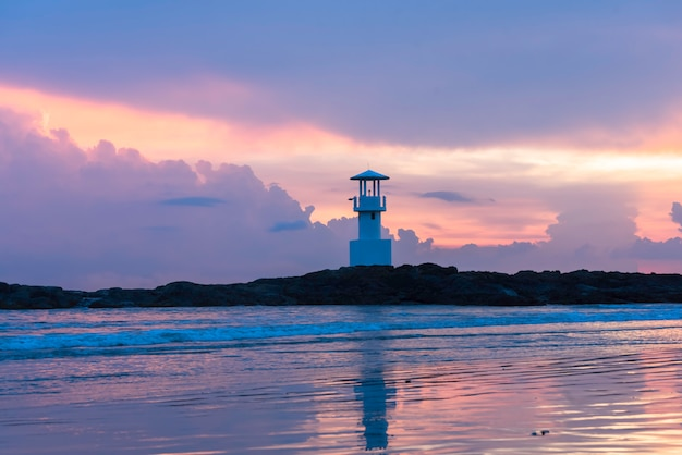 Lighthouse at twilight with reflection.