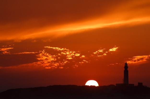 Lighthouse with colorful sunset with sun on skyline