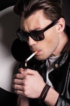 담배에 불을 붙입니다. 담배를 피우는 가죽 재킷을 입은 잘생긴 남성 모델