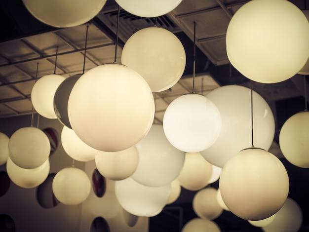 黒い背景に天井からぶら下がっている照明ボール