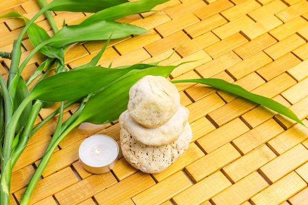 木製マットの上の白い石のピラミッドと竹の枝の近くの照明キャンドル