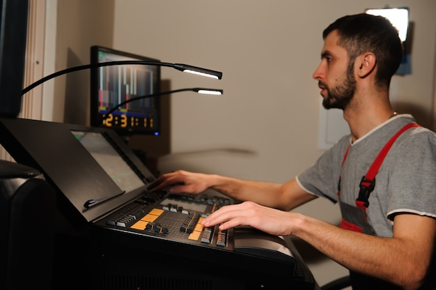 A lighting engineer works with lights technicians control on the concert show. professional light mixer, mixing console. equipment for concerts
