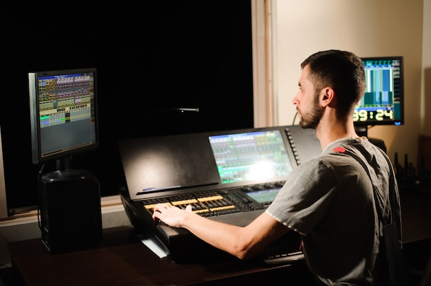 A lighting engineer works with lights technicians control