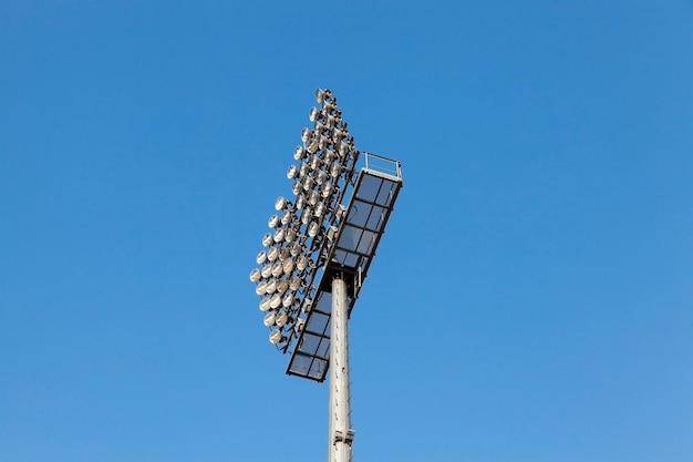 기둥에 장착 된 조명 장비. 위치-경기장, 푸른 하늘