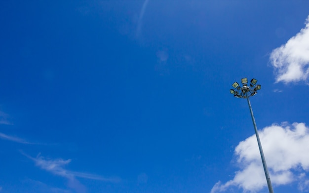 A lighting lamp on a pole against the blue sky, sport light with blue sky cloud background