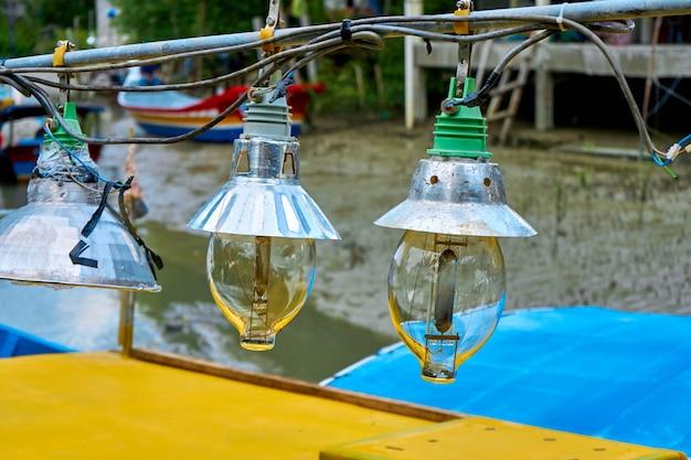 Осветительные лампы на старой маленькой рыбацкой лодке.