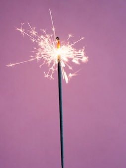 Lighting sparkler on pink background