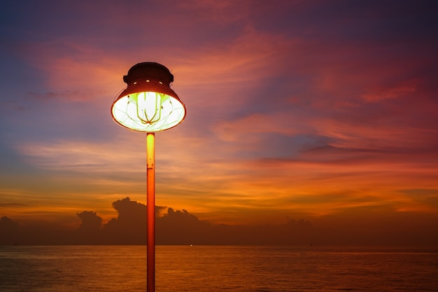 Lighting of warm lamp or yellow hid lamp and lighting of sunset at sea with beautiful sky