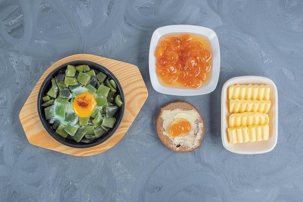 Слегка приготовленные бобы с яичницей-болтунью, сливочным маслом, ломтиками масла и вареньем из белой вишни на мраморном столе.
