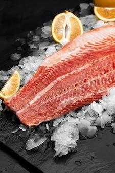 살짝 소금에 절인 송어. 검은 배경에 요리 재료, 허브, 레몬을 넣은 신선한 생선 필레, 측면 전망.