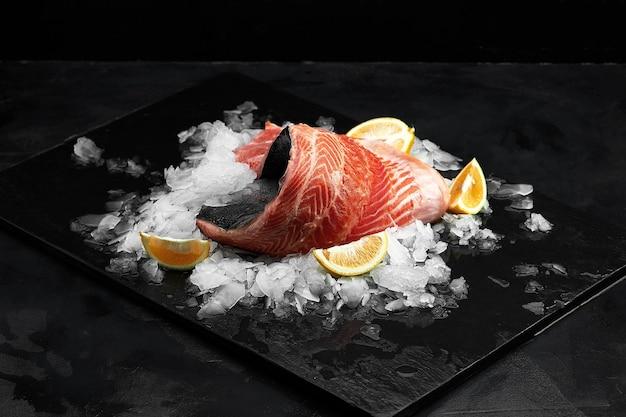 Слабосоленая форель. филе свежей рыбы с кулинарными ингредиентами, зеленью и лимоном на черном фоне, вид сбоку.