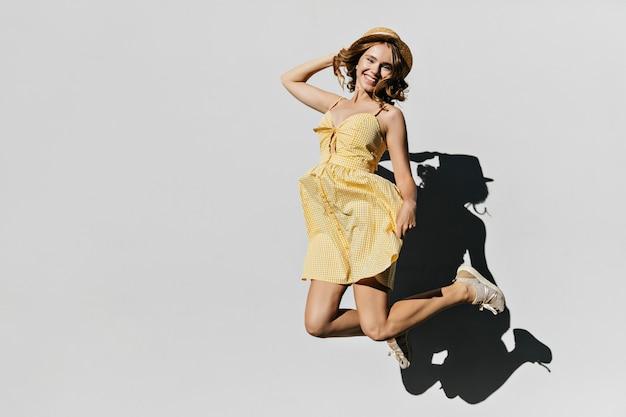 Signora bionda leggermente abbronzata che salta ed esprime felicità. felice donna bianca con cappello e vestito giallo divertirsi.