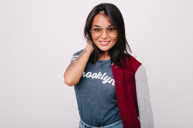 Ragazza bruna leggermente abbronzata con tatuaggio sul braccio in posa con un sorriso isolato. modello femminile dai capelli neri in bicchieri e bombardiere divertendosi.