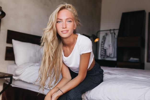 침대에 앉아 긴 헤어 스타일으로 가볍게 무두질 귀여운 여자. 아침에 포즈를 취하는 여자.