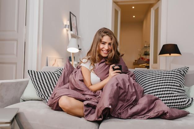 Слегка загорелая восторженная женщина сидит с фиолетовым пледом на диване и улыбается