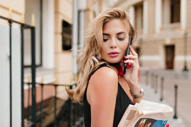 目を閉じて電話で誰かを聞いている長いブロンドの髪を持つ軽く日焼けした女性モデル