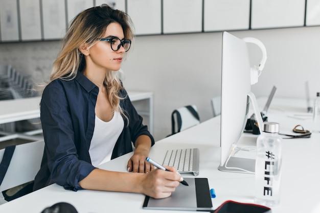 아늑한 사무실에서 컴퓨터로 작업하는 안경과 검은 셔츠에 가볍게 무두질 소녀