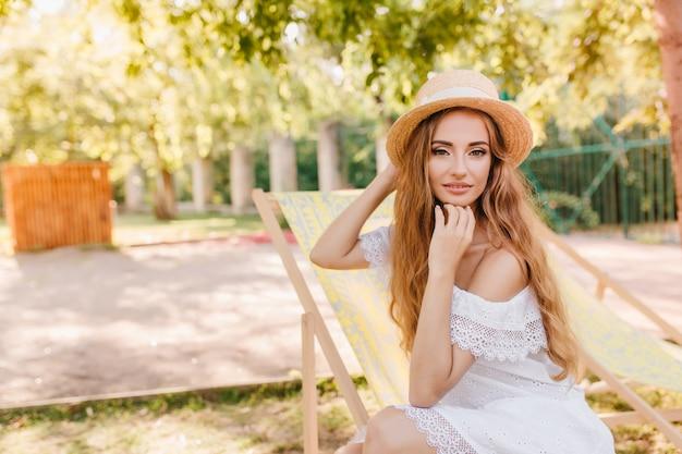 Ragazza leggermente abbronzata in abito di pizzo vintage seduto sulla sedia da giardino e in posa con interesse. bella giovane donna in cappello di paglia di estate che si rilassa sotto il cielo aperto e che sorride delicatamente.
