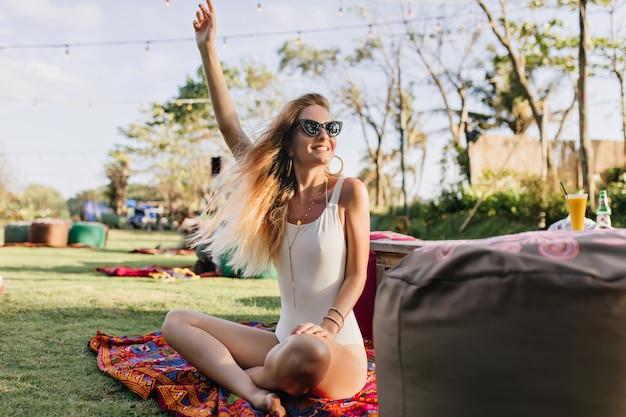 芝生の上に座って手を振っている水着の日焼けした女性。公園で楽しんでいるブロンドの髪を持つ素敵な若い女性の屋外の肖像画。