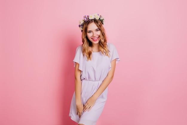 Donna leggermente abbronzata in ghirlanda di fiori alla moda che ride durante il servizio fotografico