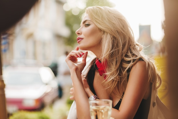 Lightly-tanned woman with pink lipstick looking away while chilling in favorite cafe in morning