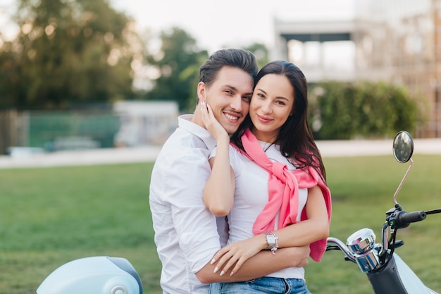 Lightly-tanned woman with pretty face sitting on scooter with husband and smiling on nature background