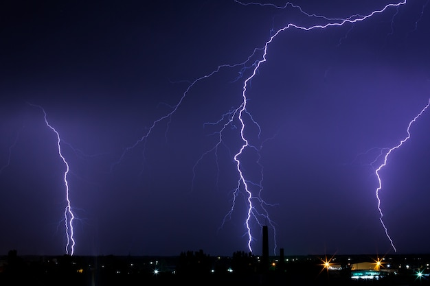 Lightning storm over the city in purple light.