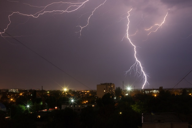 Lightning storm over the city in purple light