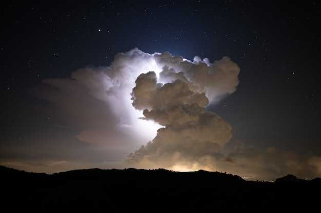 Lightning strikes inside a cloud cluster at night seen from far away