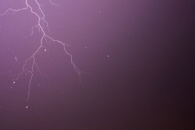 Lightning and thunderstorm on purple sky background with raindrops.
