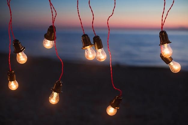海を背景にした夜のライトとライト。ボケ