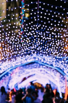 Lights bokeh with blur people in background. festival for christmas
