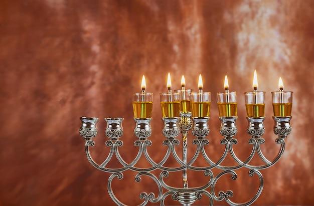Зажигает свечи в шестой день еврейского праздника ханука. горят свечи от меноры